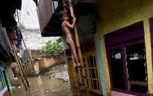 Dua anak bermain banjir yang menggenangi pemukiman mereka di Kampung Melayu, Jakarta, Jumat (23/1)