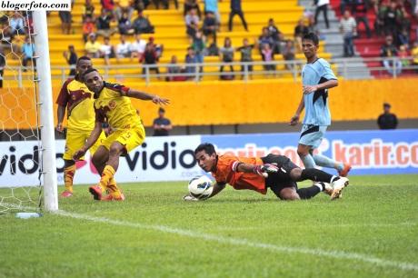 Pemain Sriwijaya FC Titus Bonai (kiri) mengejar bola yang berhasil ditepis Kiper Persela Lamongan Choirul Huda (kanan) pada semi final Sriwijaya Media Cup di Stadion Gelora Sriwijaya, Jakabaring, Palembang, Sumsel, Minggu (25/1).  ANTARA FOTO/Feny Selly